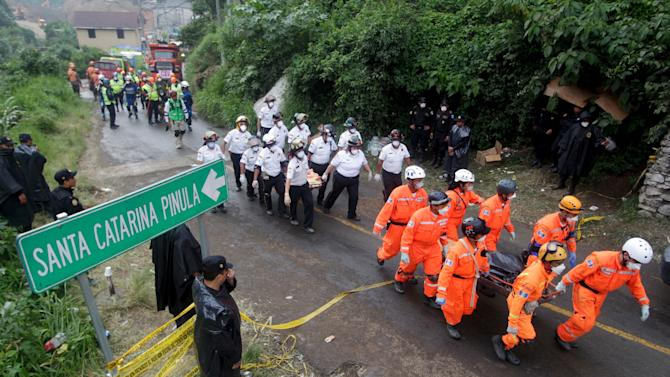 Rescue team members carry the bodies of mudslide victims toward the coroner's truck, in Santa Catarina Pinula