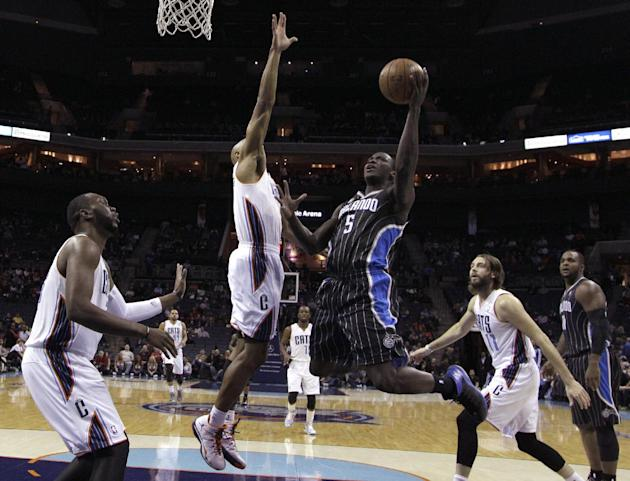 Orlando Magic's Victor Oladipo, center, drives between Charlotte Bobcats' Gerald Henderson, second from left, and Josh McRoberts, second from right, during the first half of an NBA basketball