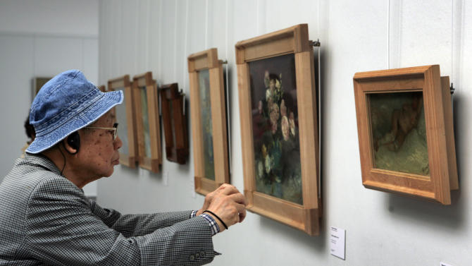 "In this photo taken May 8, 2008, a man moves close to take a photo of the early 1887 painting ""Nude Woman Reclining"" by Vincent van Gogh at Kroeller-Mueller museum, Otterlo, eastern Netherlands. With the Van Gogh Museum in Amsterdam closed for renovations, the world's second-largest collection of the tortured Dutch master's work is stepping into the limelight. The lesser-known Kroeller-Mueller museum in the eastern Netherlands has revamped the layout of its central rooms, giving more space and focus to many of its top works. (AP Photo/Peter Dejong)"