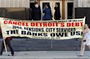Protesters carry a banner calling for Detroit's debt to be cancelled as people enter the federal courthouse for day one of Detroit's municipal bankruptcy hearings in Detroit