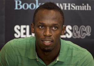 "Jamaican athlete Usain Bolt poses for photographers as he signs copies of his autobiography, ""Faster than Lightning,"" at Selfridges in central London"