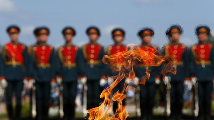 Russian servicemen are seen through the Eternal Flame during a ceremony to mark the Paratroopers Day in central St. Petersburg