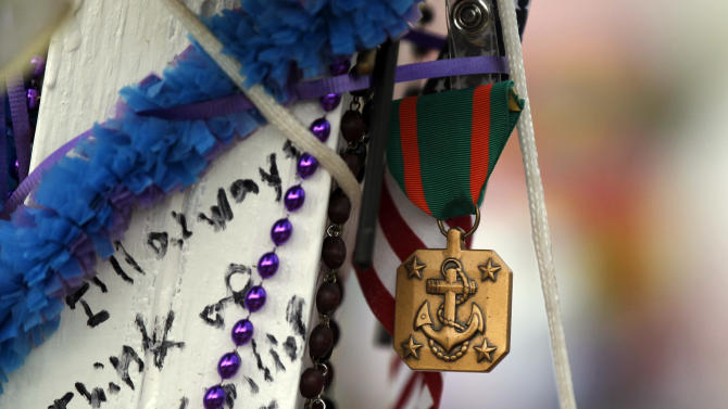 A Navy and Marine Corps Achievement Medal is pinned to cross for John Larimer, who was in the U.S. Navy, on Sunday, July 29, 2012 at a memorial across from the movie theater in Aurora, Colo. where twelve people were killed and more than 50 wounded in a shooting attack on July 20. (AP Photo/Alex Brandon)