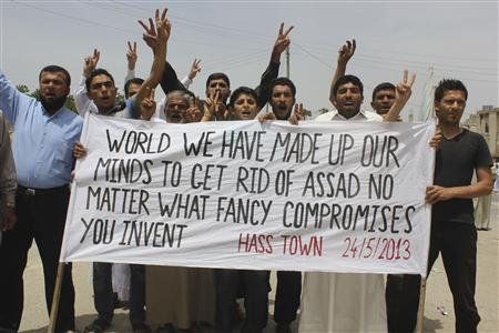 Demonstrators carry a banner during a protest against Syria's President Bashar al-Assad in Hass town, near Idlib