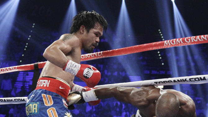 Manny Pacquiao, left, from the Philippines, drives Timothy Bradley, from Palm Springs, Calif., into the ropes in the third round of their WBO welterweight title fight Saturday, June 9, 2012, in Las Vegas. (AP Photo/Julie Jacobson)
