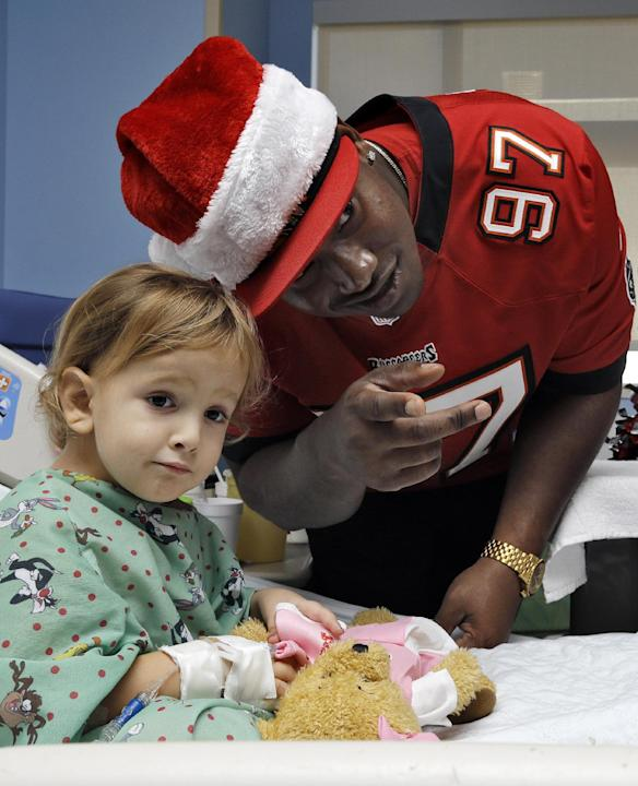 Tampa Bay Buccaneers defensive tackle Akeem Spence (97) tries to coax a smile out of Alessandra Spagnola after giving her a teddy bear during a team visit to All Children's Hospital Tuesday, Dec.