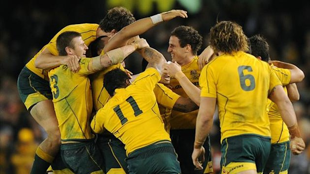 Australian players are jubilant after their teammate Mike Harris (3rd-R) had kicked the winning points