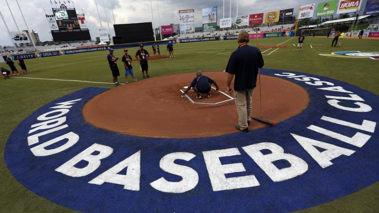 The batting cage is prepared by groundsmen before the start of the World Baseball Classic first round game between Venezuela and the Dominican Republic in San Juan, Puerto Rico, Thursday, March 7, 2013. (AP Photo/Andres Leighton)