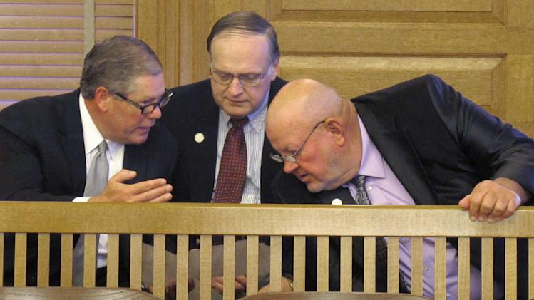 In this May 30, 2013 photo, Jeff Freeman, left, a senior federal lobbyist for the National Rifle Association and former Kansas legislator, confers with Kansas state Reps. Ed Bideau, center, of Chanute, and Larry Hibbard, right, of Toronto, before a GOP caucus in the Statehouse in Topeka, Kan. The two Republican lawmakers supported an NRA-backed bill to restrict the use of state funds for lobbying on gun-control issues, which Gov. Sam Brownback signed into law hours after they huddled. (AP Photo/John Hanna)