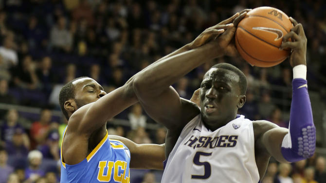 Washington's Aziz N'Diaye (5) battles for the ball with UCLA's Shabazz Muhammad during the first half of an NCAA college basketball game, Saturday, March 9, 2013, in Seattle. (AP Photo/Ted S. Warren)