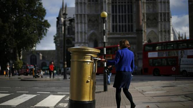 A woman post a letter into a golden Royal Mail post box in central London