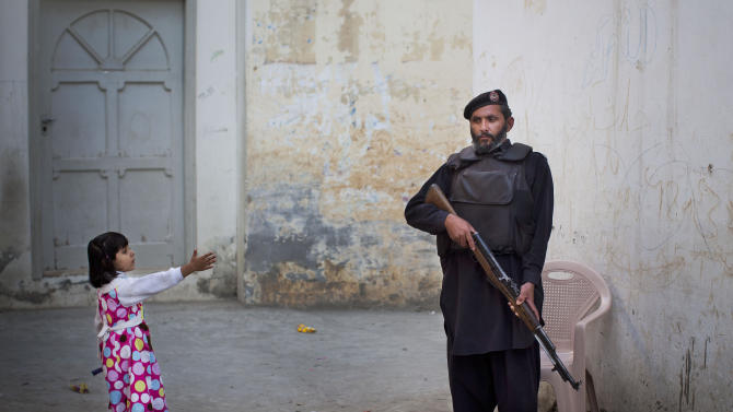 In this Nov. 15, 2012 photo, a young girl reaches out to greet a Pakistani policeman securing the road outside Kainat Riaz's home in Mingora, Swat Valley, Pakistan. Security stepped up after Kainat was wounded by the same Taliban gunman who shot Malala Yousufzai and 13-year-old Shazia Ramazan on Oct. 8 on their way home from school. Malala was shot for her outspoken insistence on girls' education. Shazia and Kainat are to return to school this week for the first time since the shooting. (AP Photo/Anja Niedringhaus)