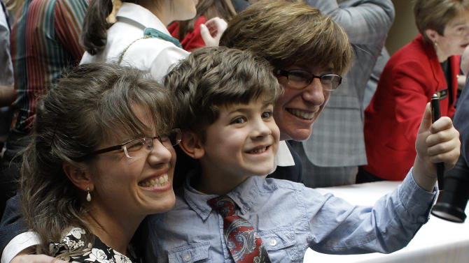 Anna Simon, left, and her partner Fran Simon hold their son Jeremy Simon, 5, who shows off his signing pen given to him by the governor at the ceremony where Colorado Gov. John Hickenlooper signed the Civil Unions Act into law at the Colorado History Museum in Denver, Colo., on Thursday, March 21, 2013. (AP Photo/Brennan Linsley)