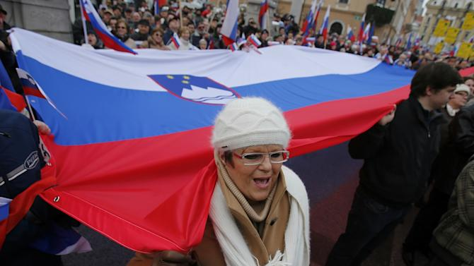 Slovenian government supporters with giant Slovenian flag take part in a political rally in downtown Ljubljana, Friday, Feb. 8, 2013. Thousands gathered to give support to Prime Minister Janez Jansa and his government. (AP Photo/Darko Bandic)