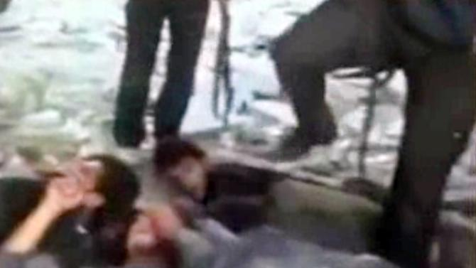 In this frame grab from amateur video taken Thursday, Nov. 1, 2012, and provided by the Syrian Observatory for Human Rights via AP video, an alleged rebel gunman steps on a captured soldier lying on the ground in Saraqeb, northern Syria. Later in the video, the rebels appear to kill the group of captured soldiers, spraying them with bullets as they lie on the ground. This image from video obtained from the Syrian Observatory for Human Rights has been authenticated based on the video and audio translated and content checked by regional experts against known locations and events, as well as being consistent with independent AP reporting. (AP Photo/Syrian Observatory for Human Rights via AP video)