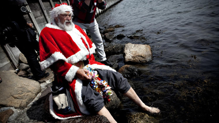 A Santa bathes his feet during the World Santa Claus Congress in front of  the Little Mermaid  statue in the harbour of Copenhagen, on Monday, July 18, 2011. The World Santa Claus Congress has taken place in the Dyrehavsbakken amusement park (usually shortened to Bakken) north of Copenhagen since 1957. (AP Photo/POLFOTO, Joachim Adrian)  DENMARK OUT