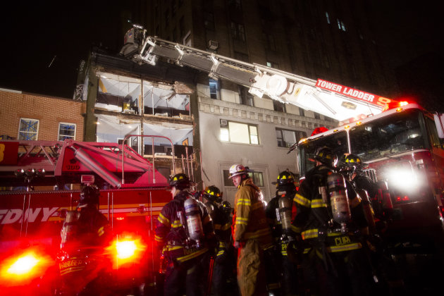 The facade of a four-story building on 14th Street and 8th Avenue collapsed onto the sidewalk as FDNY firefighters respond, Monday, Oct. 29, 2012, in New York. Hurricane Sandy continued on its path Mo