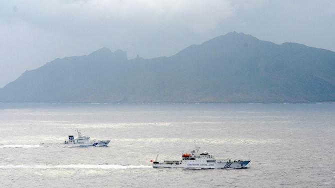 A  Japan Coast Guard vessel, left, sails along with a Chinese surveillance ship, right, near disputed islands, rear, called Senkaku in Japan and Diaoyu in China in the East China Sea Tuesday, April 23, 2013. A group of Japanese ultra-nationalists planned Tuesday to approach the islands on several fishing vessels and pleasure boats. The visit adds to risks of confrontation, however, with Chinese vessels circulating in the area. (AP Photo/Kyodo News) JAPAN OUT, MANDATORY CREDIT, NO LICENSING IN CHINA, HONG KONG, JAPAN, SOUTH KOREA AND FRANCE