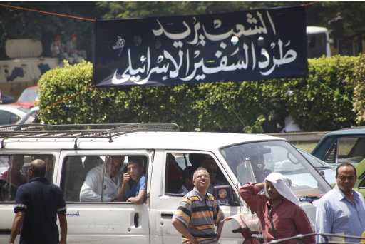 Egyptians pass under an Arabic banner with the phrase