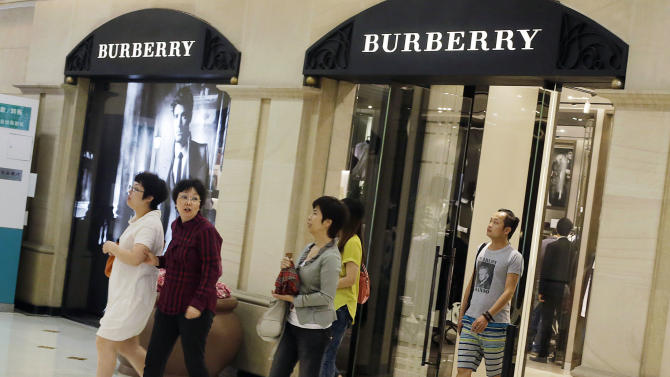 Shoppers exit a Burberry shop Wednesday, June 13, 2012, in Shanghai, China. Chinese consumers can afford to splash out more on higher quality products, but also expect better value for money than in the past, according to a study by the American Chamber of Commerce. (AP Photo/Eugene Hoshiko)