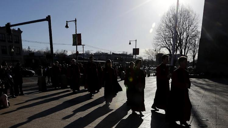 FILE - The sun casts shadows of clergy on the ground as they head into Marsh Chapel in Boston on Wednesday, April 17, 2013 before a vigil for Boston University student Lingzi Lu, who was killed in the Boston Marathon explosions. (AP Photo/Julio Cortez)