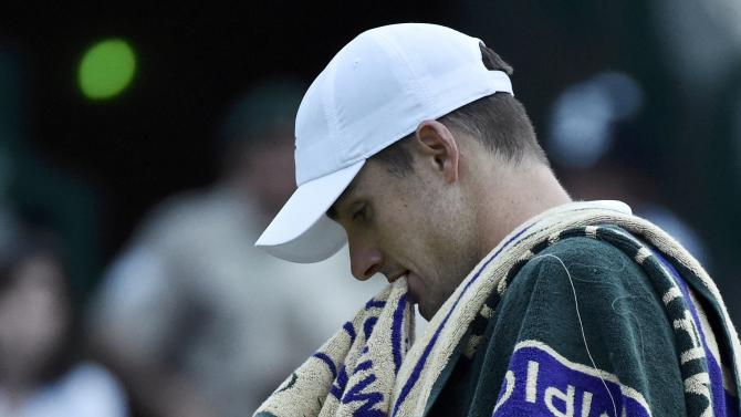 John Isner of the U.S.A. bites his towel during his match against Marin Cilic of Croatia at the Wimbledon Tennis Championships in London