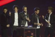 Pop group One Direction react after being awarded the Global Success award at the BRIT Awards, celebrating British pop music, at the O2 Arena in London February 20, 2013. REUTERS/Dylan Martinez
