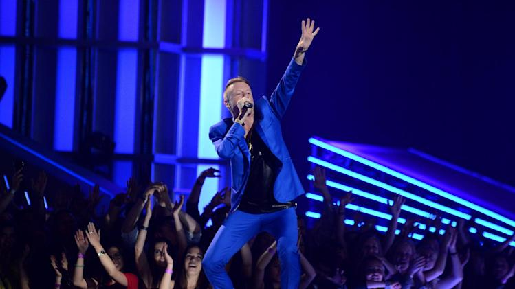 """FILE - This April 14, 2013 file photo released by MTV shows rapper Macklemore of Macklemore & Ryan Lewis, performing at the MTV Movie Awards in Sony Pictures Studio Lot in Culver City, Calif. The song by Macklemore & Ryan Lewis feat. Ray Dalton, """"Can't Hold Us,"""" was the top streamed track on Spotify from Monday, May 20, to Sunday, May 26. (AP Photo/ MTV, Jordan Strauss, file)"""