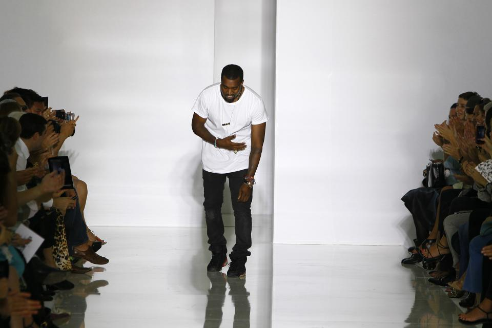 Rap singer Kanye West acknowledges applause at the end of his spring-summer 2012 ready-to-wear collection presented Saturday, Oct.1, 2011 in Paris. (AP Photo/Francois Mori)