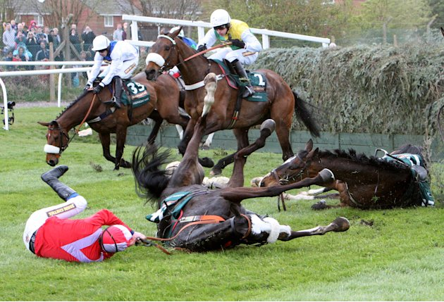 According to Pete ridden by Harry Haynes, left, falls after jumping Becher's Brook during the Grand National at Aintree Racecourse, Liverpool, England, Saturday April 14, 2012. British Grand National