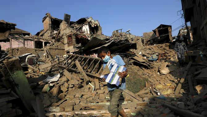 Earthquake survivor carries salvaged belongings from his family's collapsed houses in Sankhu