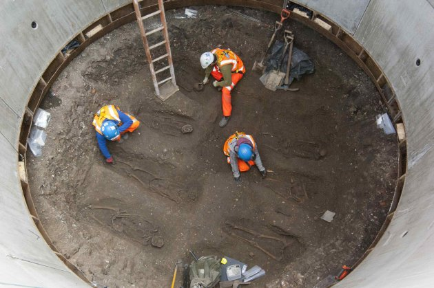 Handout photograph of archaeologists working on unearthed skeletons in the Farringdon area of London