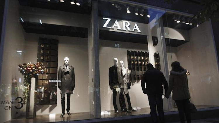 A couple looks at a Zara shop window in central Athens