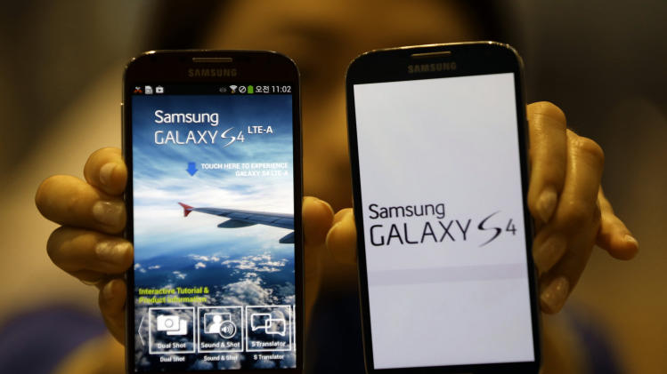 An employee of Samsung Electronics holds the Galaxy S4 LTE-A smartphones at a showroom of its headquarters in Seoul, South Korea, Friday, July 5, 2013. Even after setting a record high profit, Samsung Electronics disappointed investors who increasingly doubt its mainstay smartphone business can maintain rapid growth. Samsung Electronics Co. on Friday estimated its April-June operating profit at a record high of 9.5 trillion won ($8.3 billion). But it fell short of forecasts by analysts who held higher expectation for the world's largest smartphone maker. (AP Photo/Lee Jin-man)