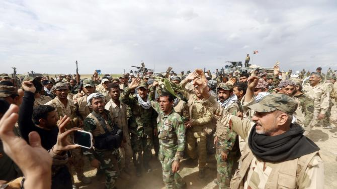 Members of the Iraqi security forces and Shiite fighters celebrate after taking control of the town Hamrin from Islamist State militants, in Hamrin in Salahuddin province