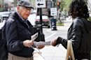 Richard Retta, 80, left, hands an anti-abortion flyer to a woman as she leaves Planned Parenthood in downtown Washington, Wednesday, April 4, 2012. Three days a week, for the past eight years, Retta has stood outside a Planned Parenthood clinic in downtown Washington, three blocks from the White House, and tried to convince women not to get abortions. (AP Photo/Jacquelyn Martin)