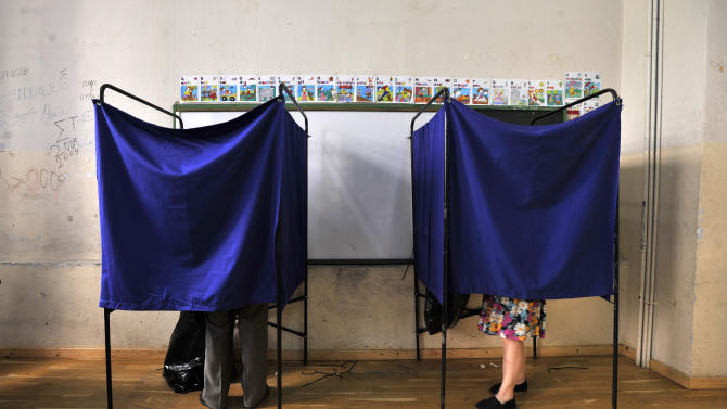 People vote inside booths during the elections in Thessaloniki, Greece, Sunday, June 17, 2012. Greeks voted Sunday for the second time in six weeks in what was arguably their country's most critical election in 40 years, with the country's treasured place within the European Union's joint currency in the balance. (AP Photo/Nikolas Giakoumidis)