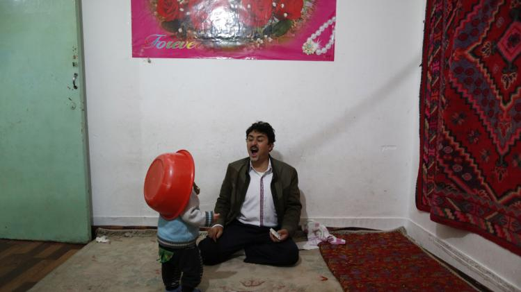 A Uighur man plays with a child at home in Shanghai