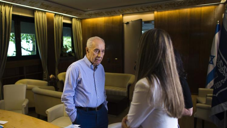 Israel's President Peres speaks with senior media adviser Frisch at the presidential residence in Jerusalem, on his last day in office,