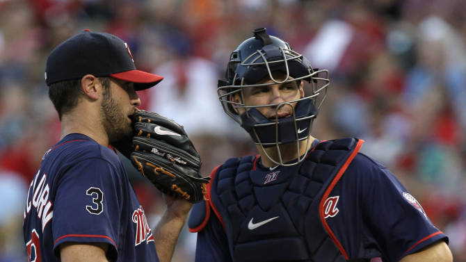 Minnesota Twins starting pitcher Nick Blackburn talks to catcher Joe Mauer on the mound after giving up a single to Texas Rangers' Michael Young in the second inning of a baseball game, Monday, July 25, 2011, in Arlington, Texas. (AP Photo/Tony Gutierrez)