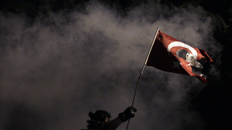 A protester holds a Turkish flag decorated with the image of Turkey's founder Mustafa Kemal Ataturk, during clashes near Taksim Square in Istanbul, late Monday, June 3, 2013. Turkish riot police launched round after round of tear gas against protesters on Monday, the fourth day of violent demonstrations, as the president and the prime minister staked competing positions on the unrest. Prime Minister Recep Tayyip Erdogan rejected the protesters' demands that he resign and dismissed the demonstrations as the work of Turkey's opposition. President Abdullah Gul, for his part, praised the mostly peaceful protesters as expressing their democratic rights. (AP Photo/Kostas Tsironis)