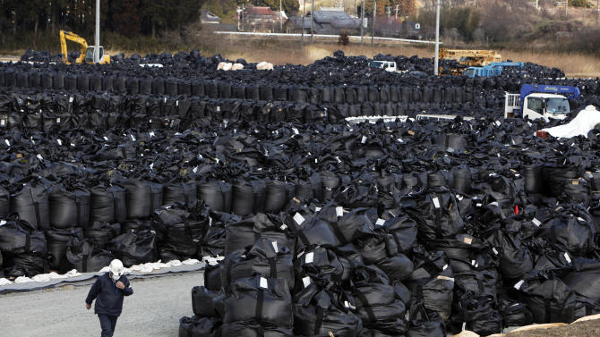 In this Tuesday, March 5, 2013 photo, a worker walks past bags of radioactive waste at a temporary waste storage site in Naraha, just outside the exclusion zone surrounding the Fukushima Dai-ichi nuclear plant in Japan. Two years after the triple calamities of earthquake, tsunami and nuclear disaster ravaged Japan's northeastern Pacific coast, radioactive and chemical contamination remains a threat.(AP Photo/Greg Baker)