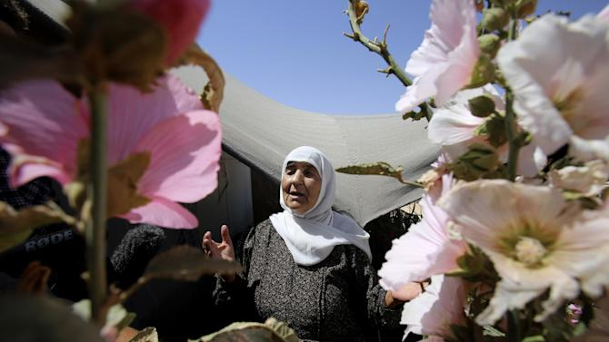 In this Wednesday, July 29, 2015 photo, an elderly Syrian refugee woman stands outside her shelter surrounded with flowers she planted, at Zaatari refugee camp, in Mafraq, Jordan. On Zaatari's anniversary this past week, the transformation from tent camp to city symbolizes the failure of rival world powers to negotiate an end Syria's war. But some say it's also a reminder that the shift from emergency aid to long-term solutions, such as setting up a water network to replace expensive delivery by truck, should have come much sooner. (AP Photo/Raad Adayleh)
