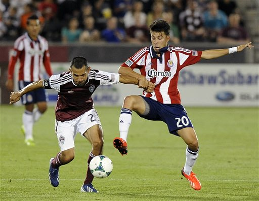 Colorado Rapids midfielder Pablo Mastroeni, left, of Argentina, fights for the ball against Chivas USA midfielder Carlos Alvarez, right, in the second half of an MLS soccer game in Commerce City, Colo