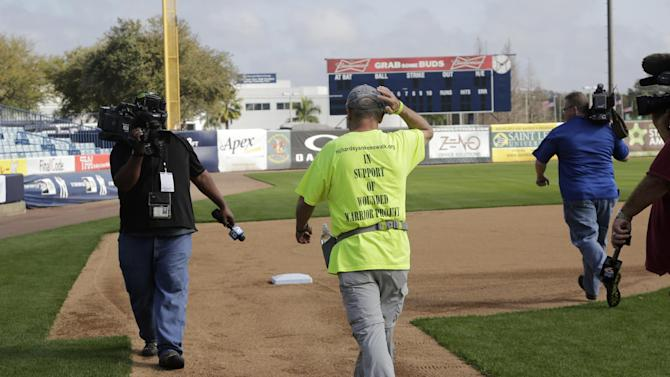 Richard J. Albero, center, sets off walking from home plate at Steinbrenner Field at a spring training baseball workout, Monday, March 2, 2015, in Tampa, Fla. Albero, whose nephew Gary Albero died in the 9/11 attacks, is walking from home plate at Steinbrenner Field in Tampa to home plate at Yankee Stadium in the Bronx. Albero is raising money for the Wounded Warrior Project. (AP Photo/Lynne Sladky)
