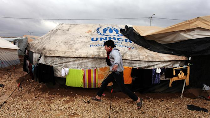 FILE - In this Tuesday, Jan. 8, 2013 file photo, A Syrian refugee boy runs to his family tent at Zaatari Syrian refugee camp, near the Syrian border in Mafraq, Jordan. The U.N. refugee agency in Jordan says there has been a spike in the number of Syrians fleeing the civil war at home and crossing into Jordan. (AP Photo/Mohammad Hannon)