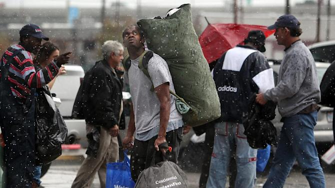 Al Horne looks up at the rain falling on homeless people waiting in line to receive a Christmas meal by The Extended Aftercare Alumni volunteers on Christmas morning, Tuesday, Dec. 25, 2012, in downtown Houston. Volunteers distributed a holiday meal, clothes, and hygiene gift packages on Christmas morning in a holiday tradition started to give people new to recovery from drug and alcohol addiction an opportunity to be of service. (AP Photo/Houston Chronicle, Mayra Beltran)