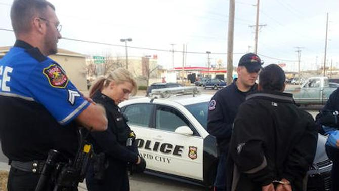 In this Nov. 21, 2012 photo provided by The Rapid City Police Department Officer Ron Terviel, left, and Officer Carmen Visian wait while paramedics check a hit-and-run suspect during a Tweetalong in Rapid City, S.D. On a virtual ridealongs on Twitter, or Tweetalongs, officers post regular updates to Twitter about what they are seeing as they perform their normal on-duty routine. The tweets, which also include photos and links to videos of the officers, can encompass an array of activities. (AP Photo/Rapid City Police, Tarah Heupel)
