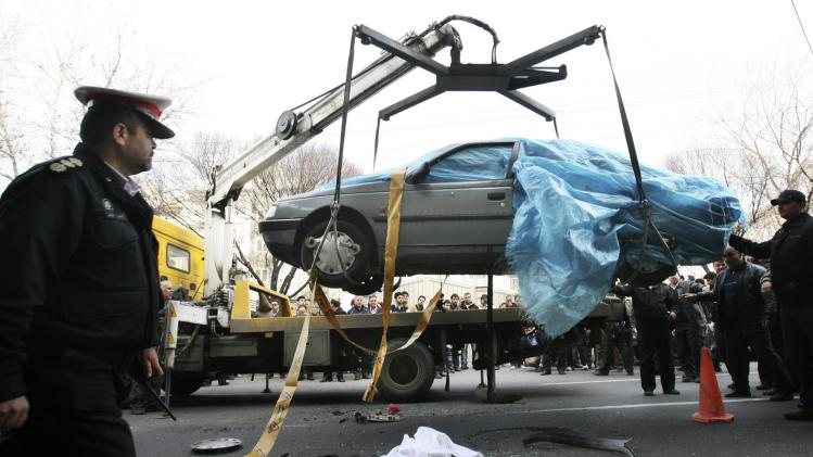 In this photo provided by the semi-official Fars News Agency, people gather around a car as it is removed by a mobile crane in Tehran, Iran, Wednesday, Jan. 11, 2012. Two assailants on a motorcycle attached magnetic bombs to the car of an Iranian university professor working at a key nuclear facility, killing him and wounding two people on Wednesday, a semiofficial news agency reported. (AP Photo/Fars News Agency, Meghdad Madadi)