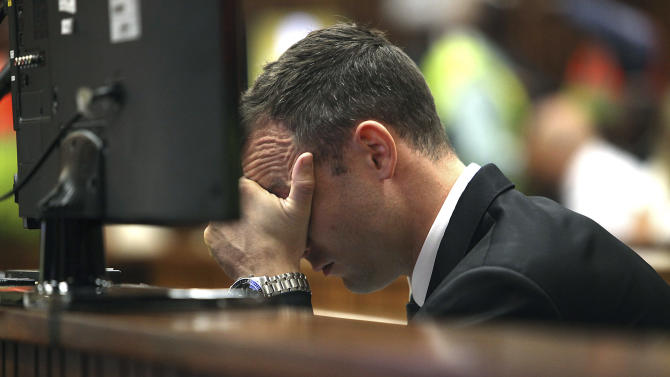 Oscar Pistorius places his hand over his face while sitting in the dock in court on the third day of his trial at the high court in Pretoria, South Africa, Wednesday, March 5, 2014. Pistorius is charged with murder for the shooting death of his girlfriend, Reeva Steenkamp, on Valentine's Day in 2013. (AP Photo/Alon Skuy, Pool)